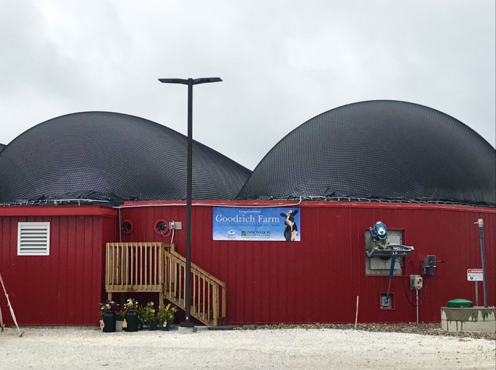 An image showing a large red building with two domes on top and a sign reading Goodrich Farm